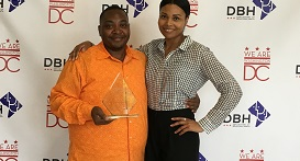 Two people standing one holds an award