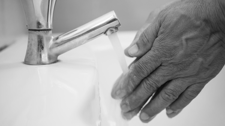 hands running under a faucet