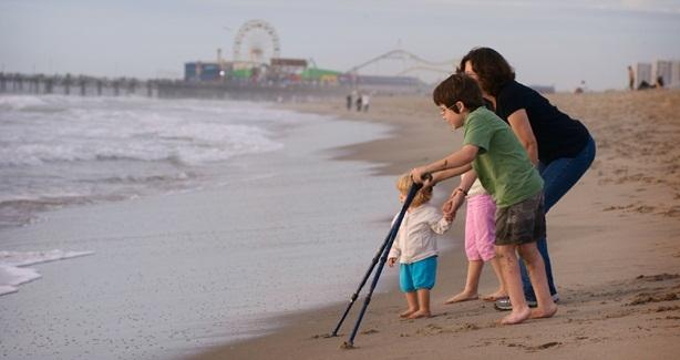 photo of family on shore, one child carries walking crutches