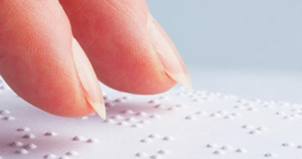 photo of person reading Braille page
