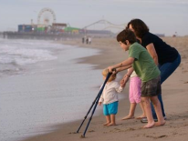Toddler, mom and child holding braces on the seashore