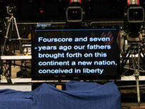 "Teleprompter in auditorium with ""Four Score"" text displayed"